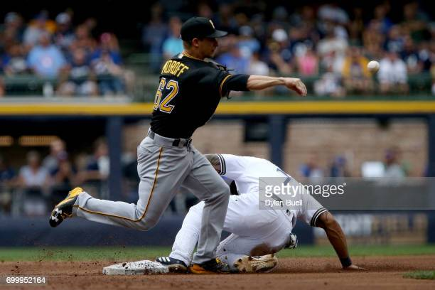Max Moroff of the Pittsburgh Pirates turns a double play past Eric Thames of the Milwaukee Brewers in the first inning at Miller Park on June 22 2017...