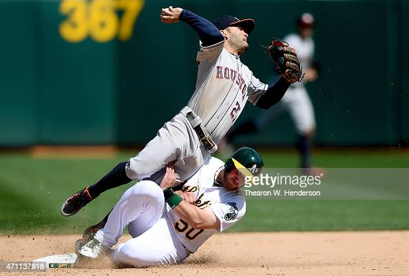 Max Muncy of the Oakland Athletics breaks up the doubleplay sliding into Jose Altuve of the Houston Astros in the bottom of the seventh inning at Oco...
