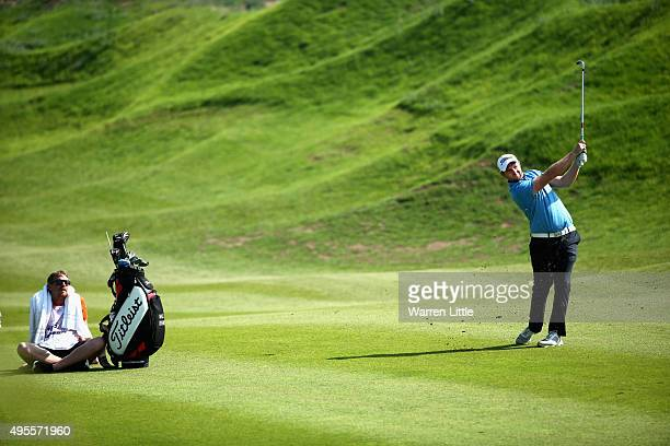 Max Orrin of England plays his second shot on the 16th hole watched by his caddie during the first round of the NBO Golf Classic Grand Final at the...