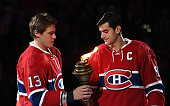 Max Pacioretty hands over the flame to Alexander Semin the Montreal Canadiens during the pre game ceremony prior to the NHL game against the New York...