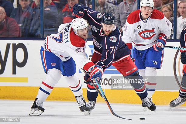 Max Pacioretty of the Montreal Canadiens and Nick Foligno of the Columbus Blue Jackets reach for a loose puck during the first period on February 26...