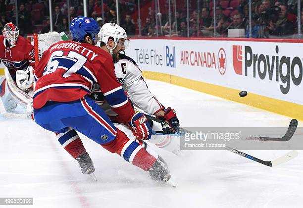Max Pacioretty of the Montreal Canadiens and Nick Foligno of the Columbus Blue Jackets fight for the puck in the NHL game at the Bell Centre on...