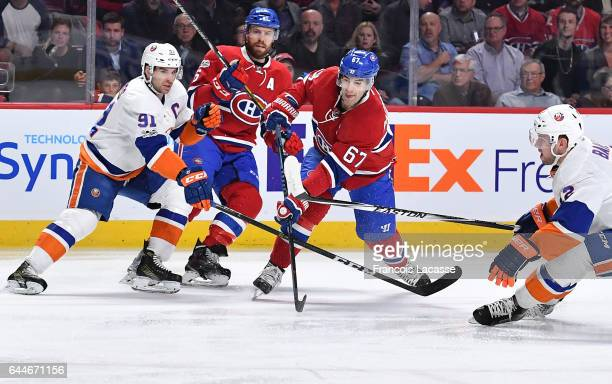 Max Pacioretty of the Montreal Canadiens clears the puck against John Tavares of the New York Islanders in the NHL game at the Bell Centre on...