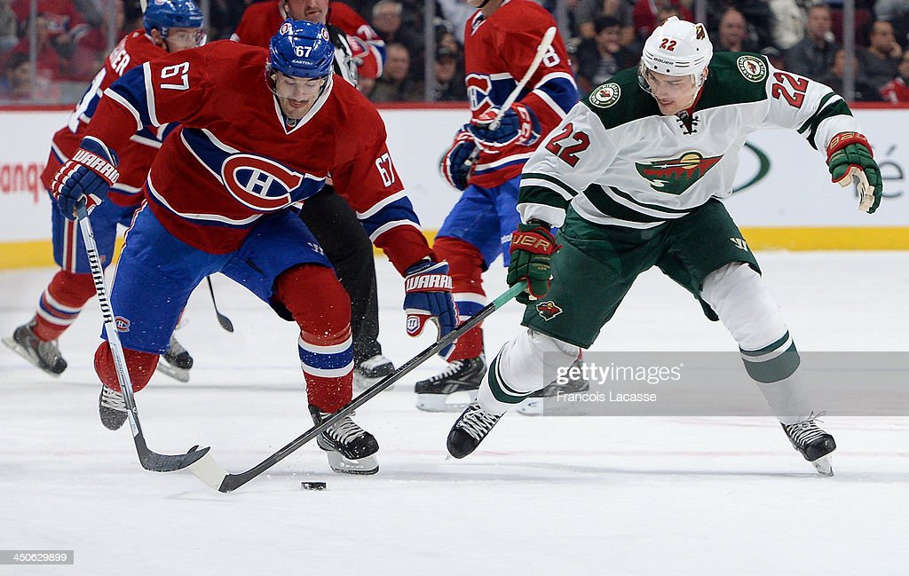 Max Pacioretty #67 of the Montreal Canadiens fights for the puck against Nino Niederreiter #22 of the Minnesota Wild during the NHL game on November 19, 2013 at the Bell Centre in Montreal, Quebec, Canada.