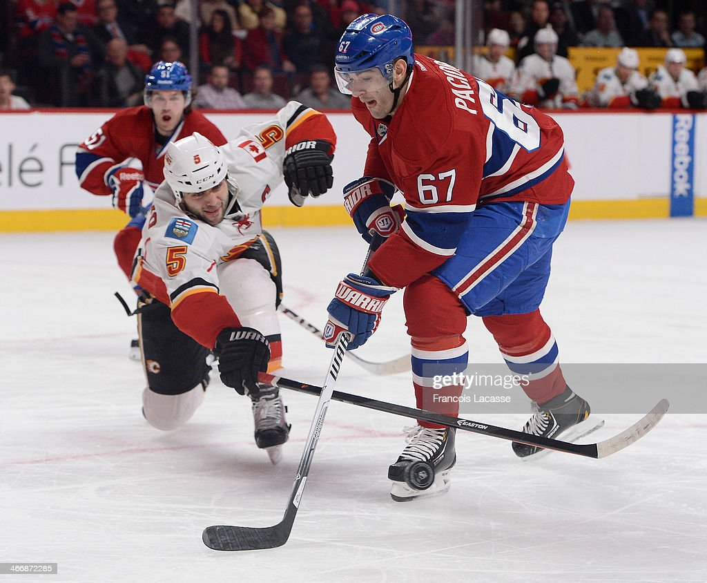 <a gi-track='captionPersonalityLinkClicked' href=/galleries/search?phrase=Max+Pacioretty&family=editorial&specificpeople=4324972 ng-click='$event.stopPropagation()'>Max Pacioretty</a> #67 of the Montreal Canadiens fights for the puck against <a gi-track='captionPersonalityLinkClicked' href=/galleries/search?phrase=Mark+Giordano&family=editorial&specificpeople=696867 ng-click='$event.stopPropagation()'>Mark Giordano</a> #5 of the Calgary Flames during the NHL game on February 4, 2014 at the Bell Centre in Montreal, Quebec, Canada.