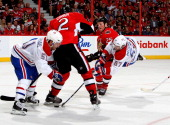Max Pacioretty of the Montreal Canadiens goes airborne and shoots the puck as Chris Neil and Jared Cowen of the Ottawa Senators defend in Game Three...