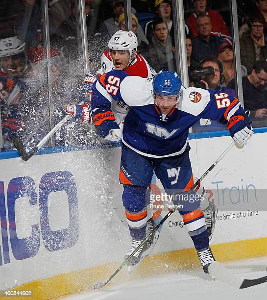 Max Pacioretty of the Montreal Canadiens is checked into the boards by Johnny Boychuk of the New York Islanders at the Nassau Veterans Memorial...
