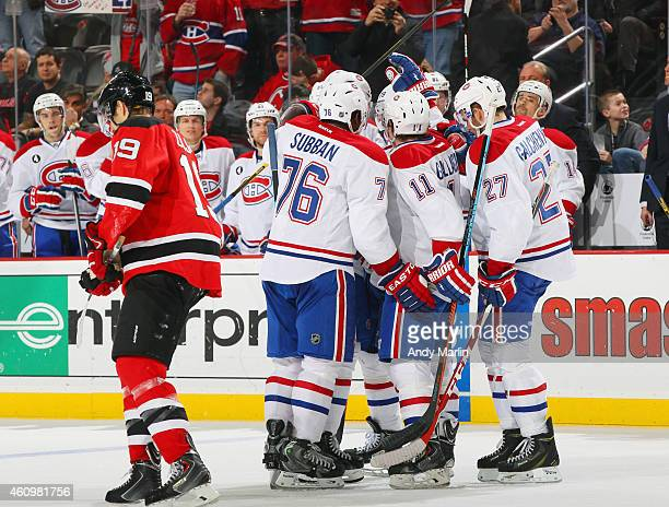 Max Pacioretty of the Montreal Canadiens is congratulated by his teammates after scoring a secondperiod goal as Travis Zajac of the New Jersey Devils...