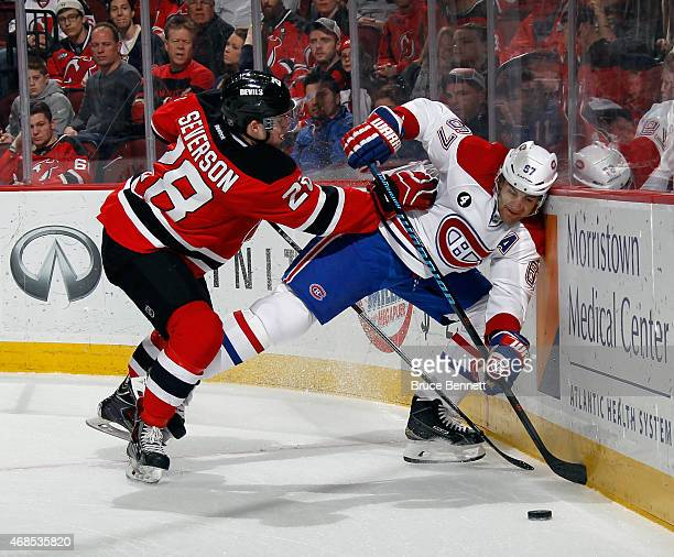 Max Pacioretty of the Montreal Canadiens is pushed into the boards by Damon Severson of the New Jersey Devils during the first period at the...