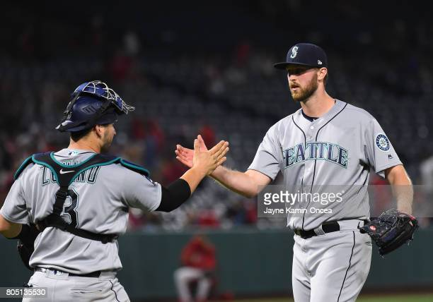 Max Povse of the Seattle Mariners shakes hands with Mike Zunino of the Seattle Mariners after earning a save in the game against the Los Angeles...