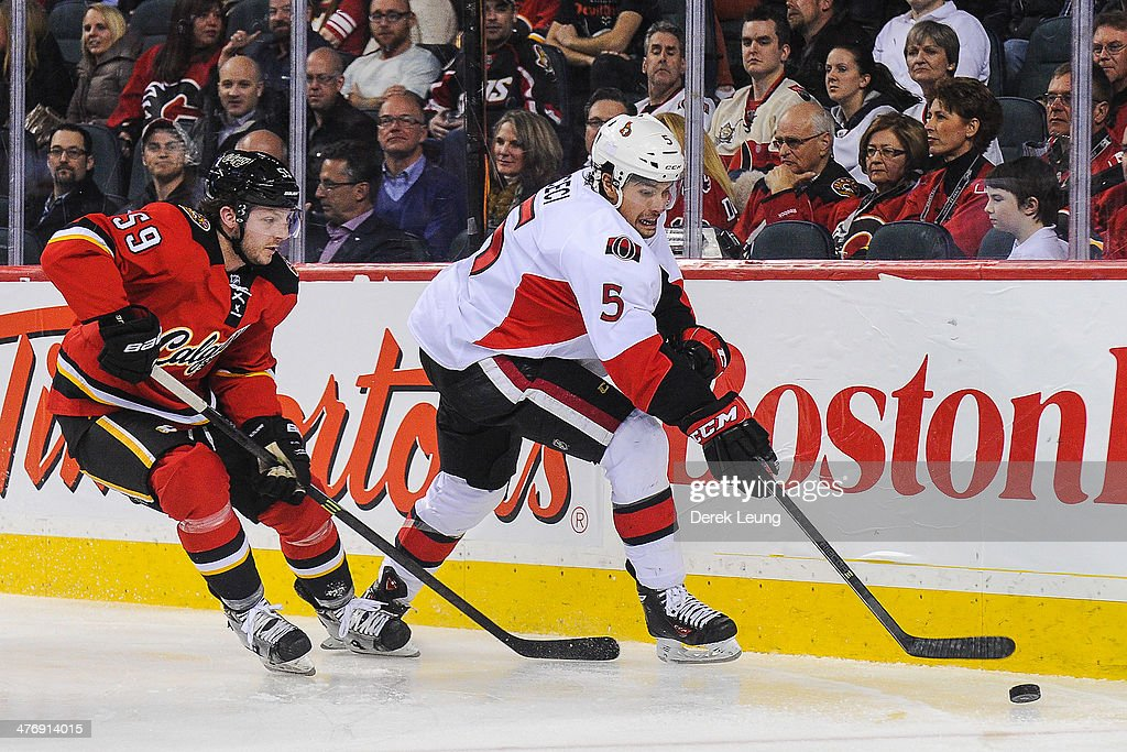 Max Reinhart #59 of the Calgary Flames chases <a gi-track='captionPersonalityLinkClicked' href=/galleries/search?phrase=Cody+Ceci&family=editorial&specificpeople=7324783 ng-click='$event.stopPropagation()'>Cody Ceci</a> #5 of the Ottawa Senators during an NHL game at Scotiabank Saddledome on March 5, 2014 in Calgary, Alberta, Canada. The Flames defeated the Senators 4-1.