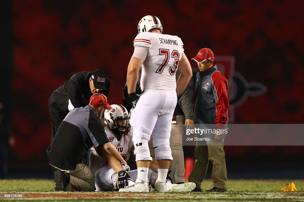 Max Scharping #73 of the Northern Illinois Huskies stands over Josh Corcoran #12 of the Northern Illinois Huskies after he gets hurt in the third quarter during the Northern Illinois v San Diego State game at Qualcomm Stadium on September 30, 2017 in San Diego, California.