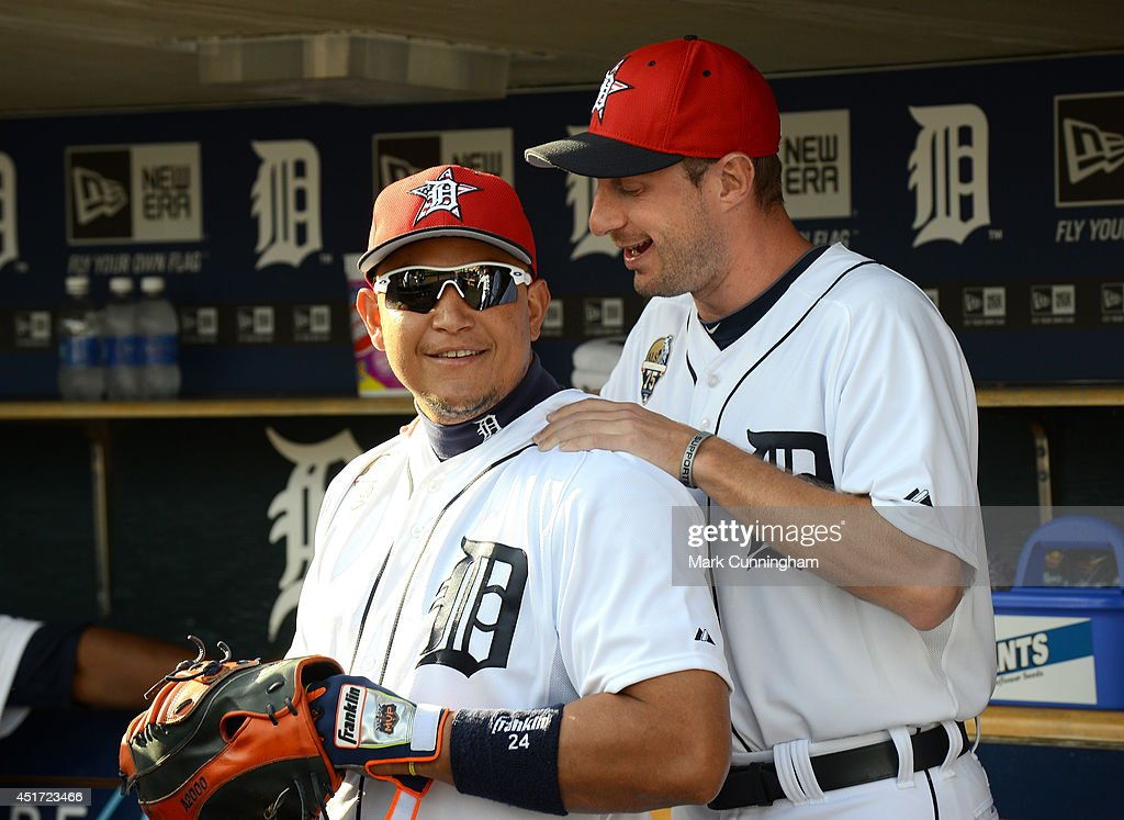 Max Scherzer #37 (R) and Miguel Cabrera #24 of the Detroit Tigers talk in the dugout while wearing special red, white and blue hats to honor Independence Day prior to the game against the Tampa Bay Rays at Comerica Park on July 4, 2014 in Detroit, Michigan. The Rays defeated the Tigers 6-3.