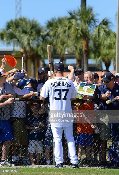 Max Scherzer of the Detroit Tigers signs autographs for fans during the spring training workout day at the TigerTown complex on February 18 2014 in...