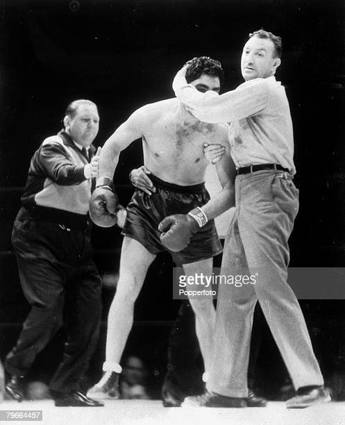 Max Schmeling of Germany is helped back to his corner by referee Arthur Dovovan after being knocked out in the 1st round by Joe Louis in their World...