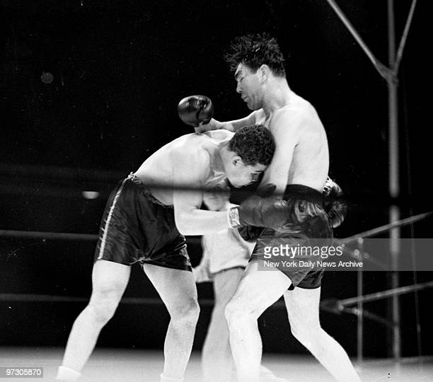 Max Schmeling versus Joe Louis I at Yankee Stadium Brutally buffeted by Max's unmerciful rights a groping Louis hangs on desperately to his tormentor...