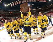Max Shuart of the Michigan Wolverines and teammates carry the MacInnes Cup around the ice after defeating the Michigan State Spartans 21 during the...
