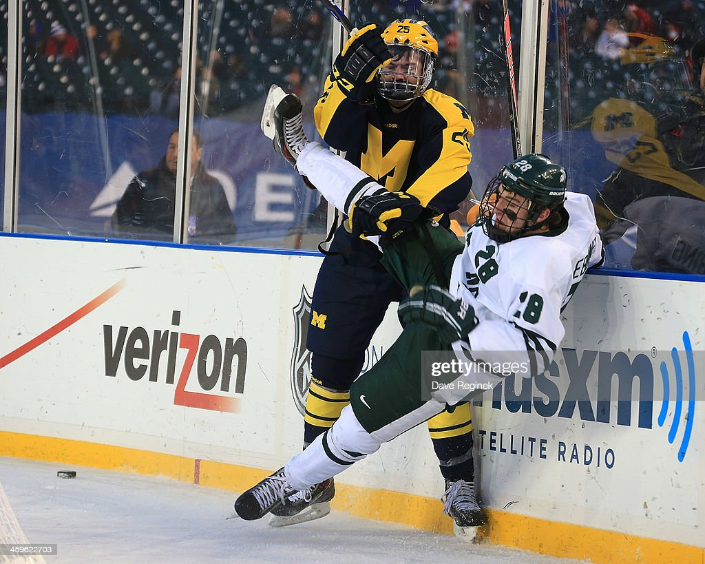 Max Shuart #25 of the University of Michigan Wolverines puts a body check on Thomas Ebbing #28 of the Michigan State Spartans during the consolation game of the Hockeytown Winter Festival Great Lakes Invitational - Day 2 played outdoors at Comerica Park on December 28, 2013 in Detroit, Michigan.