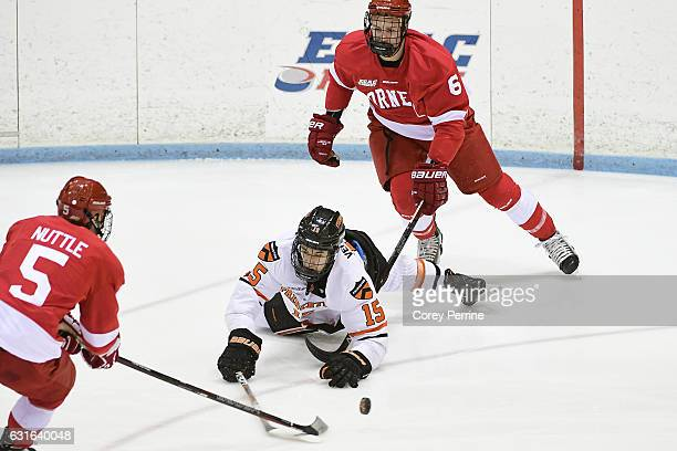 Max Veronneau of the Princeton Tigers loses his footing in front of Matthew Nuttle and Holden Anderson of the Cornell Big Red during the first period...