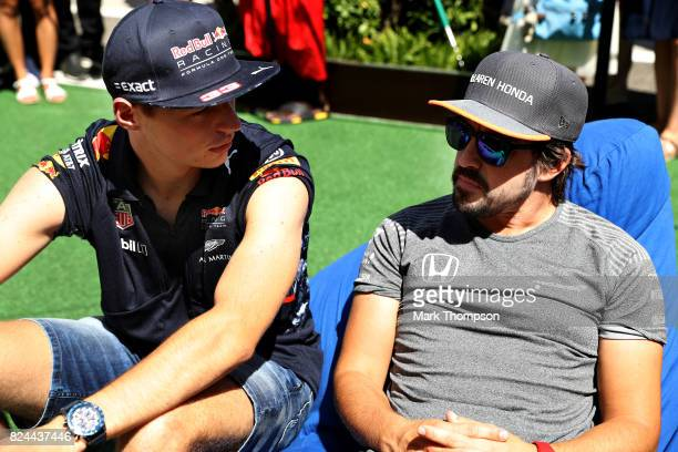 Max Verstappen of Netherlands and Red Bull Racing and Fernando Alonso of Spain and McLaren Honda talk in the Paddock before the Formula One Grand...