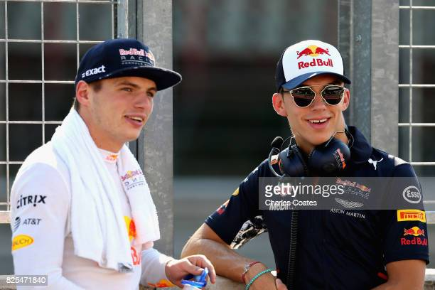 Max Verstappen of Netherlands and Red Bull Racing and Pierre Gasly of France and Red Bull Racing look on from the pit wall during day one of F1...