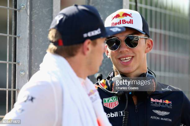 Max Verstappen of Netherlands and Red Bull Racing and Pierre Gasly of France and Red Bull Racing talk on the pit wall during day one of F1 inseason...
