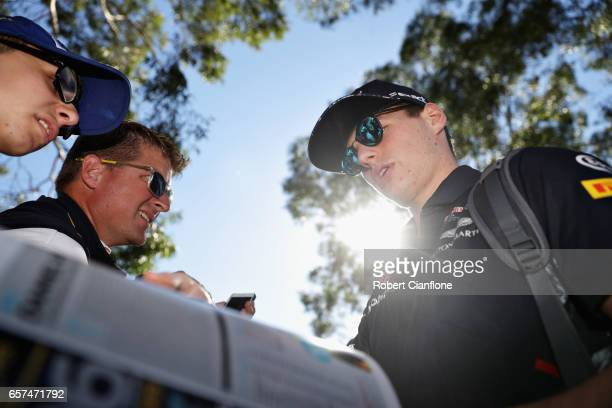 Max Verstappen of Netherlands and Red Bull Racing arrives at the circuit and ssigns autographs for fans during final practice for the Australian...