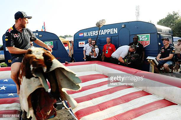 Max Verstappen of Netherlands and Red Bull Racing controls a mechanical bull while a fan tries to hold on after practice for the Formula One Grand...