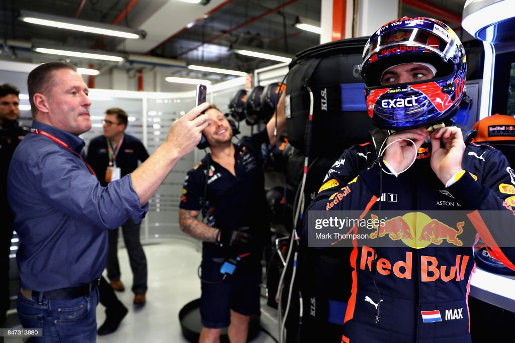 Max Verstappen of Netherlands and Red Bull Racing prepares to drive as his father Jos Verstappen takes a photo during practice for the Formula One Grand Prix of Singapore at Marina Bay Street Circuit on September 15, 2017 in Singapore.