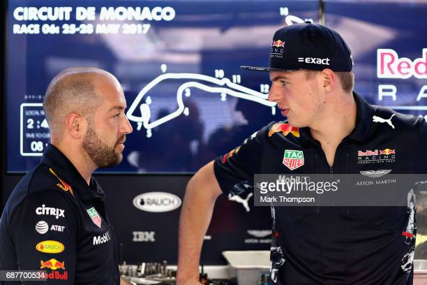 Max Verstappen of Netherlands and Red Bull Racing talks with a Red Bull Racing team member in the garage during previews for the Monaco Formula One...