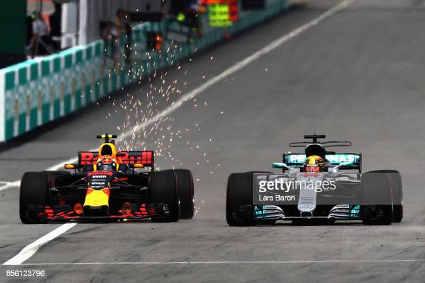 Max Verstappen of the Netherlands driving the Red Bull Racing Red BullTAG Heuer RB13 TAG Heuer battles with Lewis Hamilton of Great Britain driving...