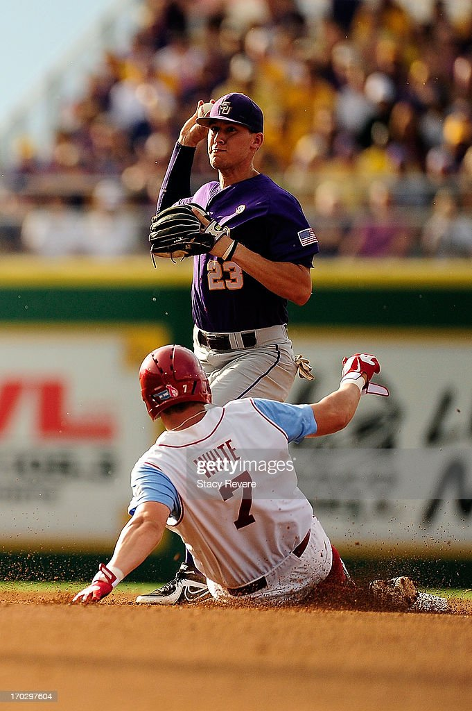 Max White #7 of the Oklahoma Sooners slides into second base as JaCoby Jones #23 of the LSU Tigers makes a throw to first base during Game 2 of the NCAA baseball Super Regionals at Alex Box Stadium on June 8, 2013 in Baton Rouge, Louisiana.