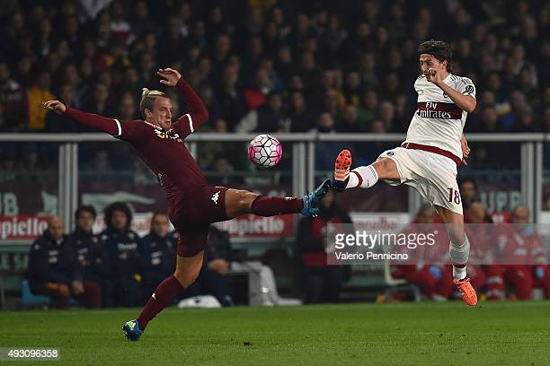 Maxi Lopez of Torino FC clashes with Riccardo Montolivo of AC Milan during the Serie A match between Torino FC and AC Milan at Stadio Olimpico di...