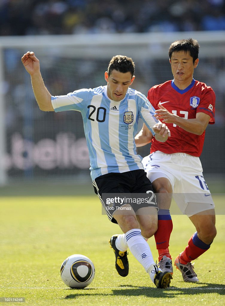 Maxi Rodriquez of Argentina challenged is by Lee YoungPyo of South Korea during the 2010 FIFA World Cup South Africa Group B match between Argentina...