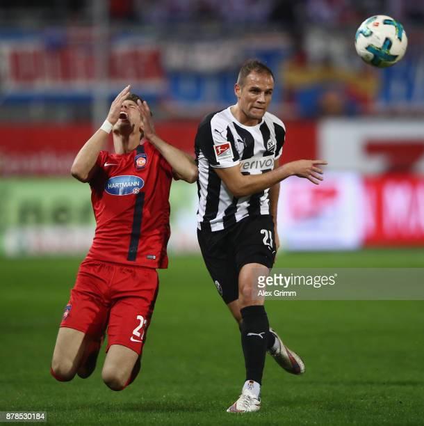 Maxi Thiel of Heidenheim is challenged by Manuel Stiefler of Sandhausen during the Second Bundesliga match between SV Sandhausen and 1 FC Heidenheim...