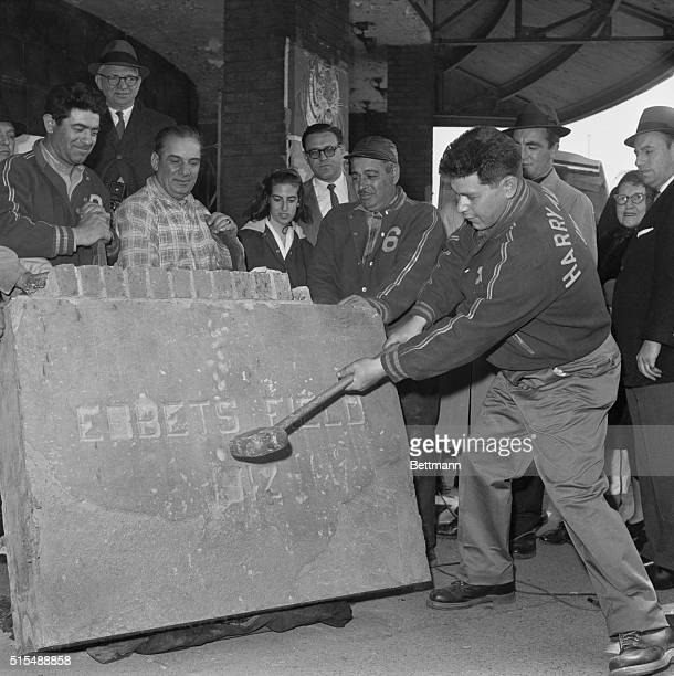 Maxie Rosenfeld takes a swing with a sledgehammer at the concrete cornerstone of Ebbets Field during an auction sale on the old stomping grounds of...