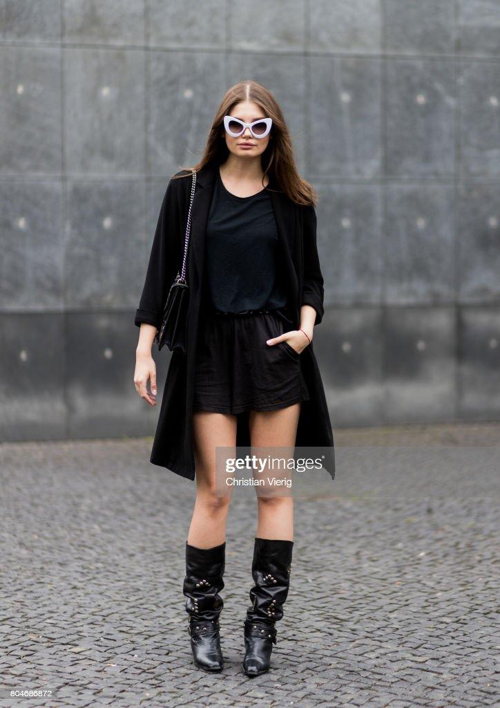 Maxilie Mlinarskij wearing a black coat from Zara, a black tshirt H&M, black shorts Cheap Monday, a Gucci bag, vintage cowboy boots, zero vintage sunglasses on June 30, 2017 in Berlin, Germany.