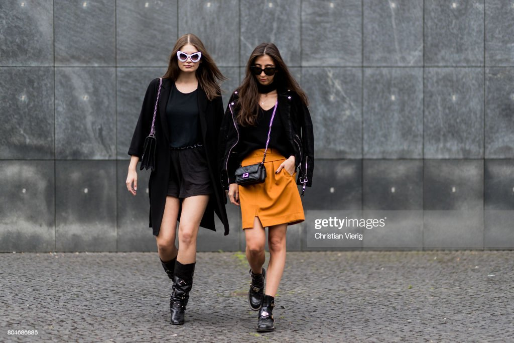 Maxilie Mlinarskij wearing a black coat from Zara, a black tshirt H&M, black shorts Cheap Monday, a Gucci bag, vintage cowboy boots, zero vintage sunglasses and Nadja Ali wearing an orange yellow skirt Lala Berlin, black leather jacket Be Edgy, a Storets knit with v neck, black Fendi bag, Balenciaga boots, Celine sunglasses on June 30, 2017 in Berlin, Germany.