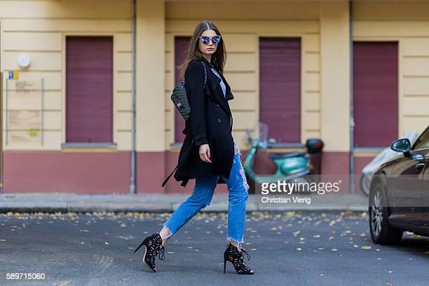 Maxilie Mlinarskij wearing a blue ripped denim jeans from Zara a black vintage coat a black Chanel bag a grey shirt from Alexander Wang sunglasses...