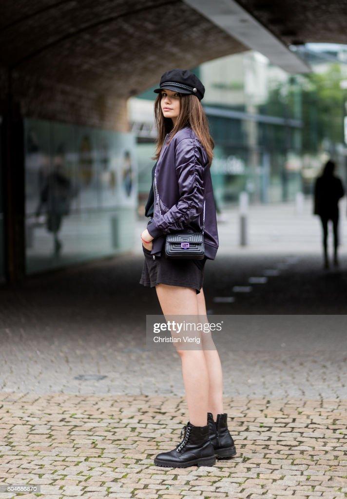 Maxilie Mlinarskij wearing a purple bomber jacket Na-kd, black Cheap Monday shorts, black H&M tshirt, black Zara boots, black Fendi bag, flat cap on June 30, 2017 in Berlin, Germany.