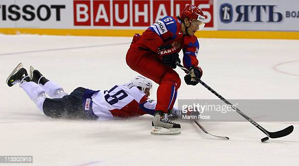 Maxim Afinogenov of Russia and Gregory Kuznik of Slovenia battle for the puck during the IIHF World Championship group A match between Russia and...