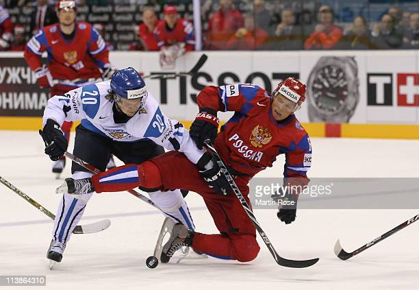 Maxim Afinogenov of Russia and Janne Pesonen of Finland battle for the puck during the IIHF World Championship qualification match between Russia and...