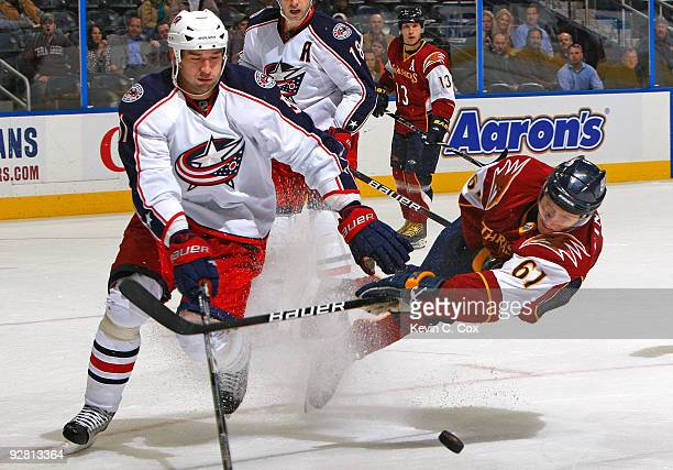 Maxim Afinogenov of the Atlanta Thrashers shoots as he is taken out in front of Fedor Tyutin of the Columbus Blue Jackets at Philips Arena on...
