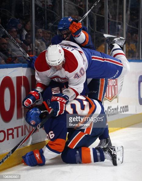 Maxim Lapierre of the Montreal Canadiens is pushed over Matt Moulson of the New York Islanders at the Nassau Coliseum on October 29 2010 in Uniondale...