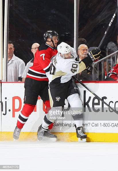 Maxim Lapierre of the Pittsburgh Penguins and Jon Merrill of the New Jersey Devils come together at the boards during the game at the Prudential...