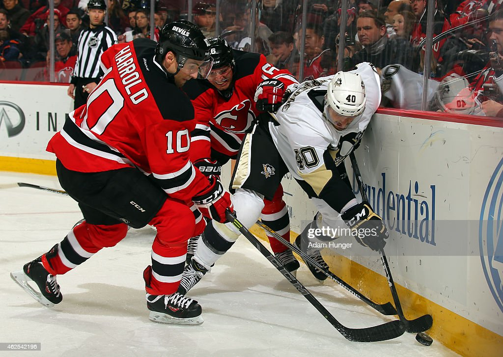 Maxim Lapierre of the Pittsburgh Penguins battles for the puck with Peter Harrold of the New Jersey Devils and Jacob Josefson of the New Jersey...