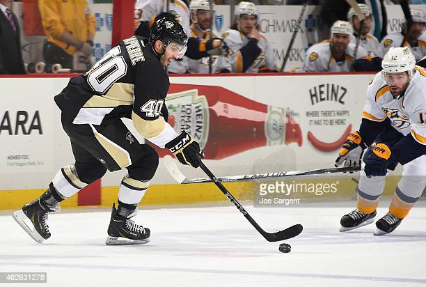 Maxim Lapierre of the Pittsburgh Penguins moves the puck up ice in front of Mike Fisher of the Nashville Predators at Consol Energy Center on...