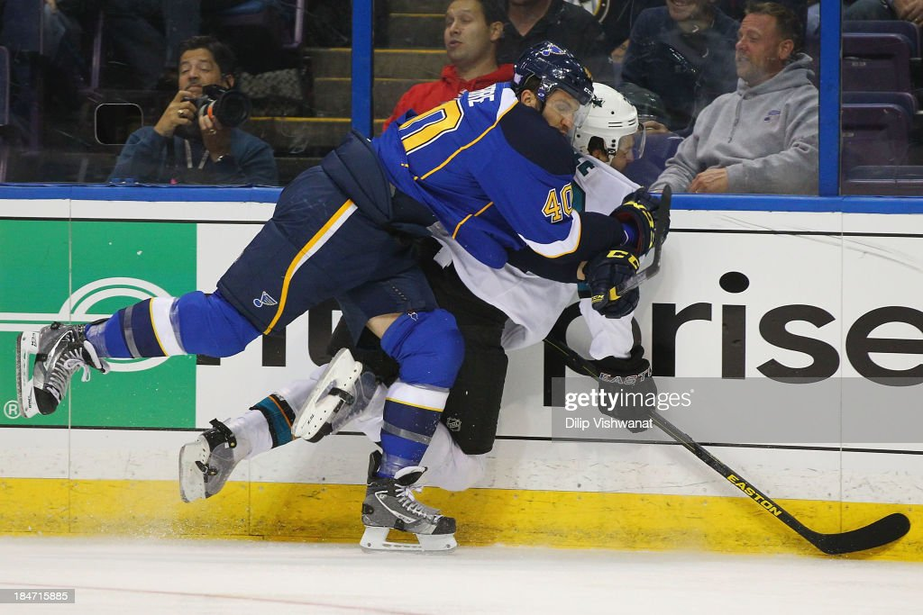 Maxim Lapierre of the St Louis Blues checks Dan Boyle of the San Jose Sharks into the boards at the Scottrade Center on October 15 2013 in St Louis...