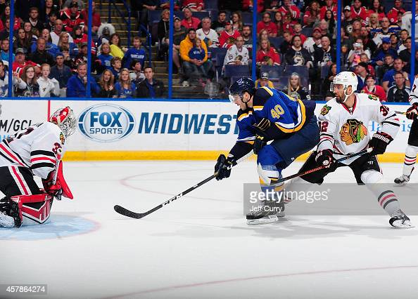 Maxim Lapierre of the St Louis Blues shoots as Antti Raanta of the Chicago Blackhawks defends the net on October 25 2014 at Scottrade Center in St...