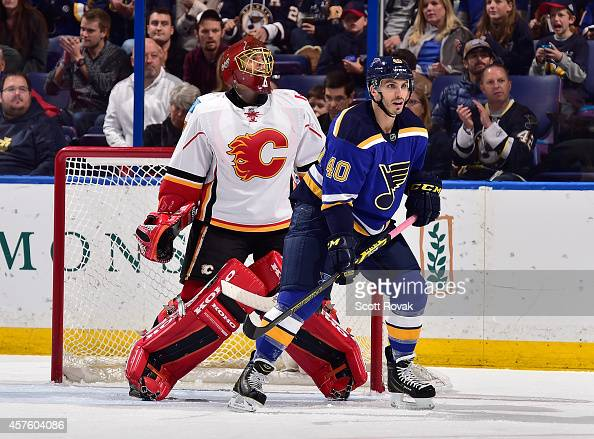 Maxim Lapierre of the St Louis Blues skates in front of Jonas Hiller of the Calgary Flames on October 11 2014 at Scottrade Center in St Louis Missouri